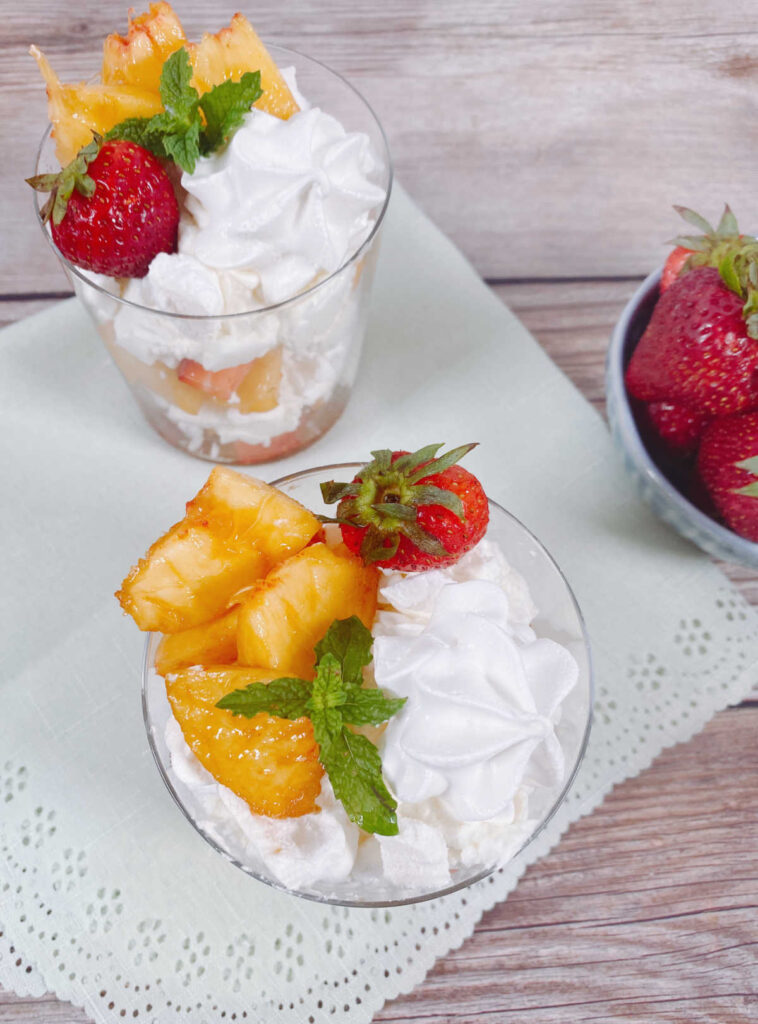 top view image of the glasses sitting on a scalloped napkin with a bowl of strawberries off to the side.