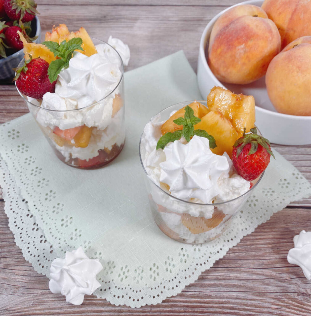 two glasses of eton mess sit on a light green scalloped napkin. A bowl of strawberries and a bowl of peaches sit off to the side, along with meringue cookies.