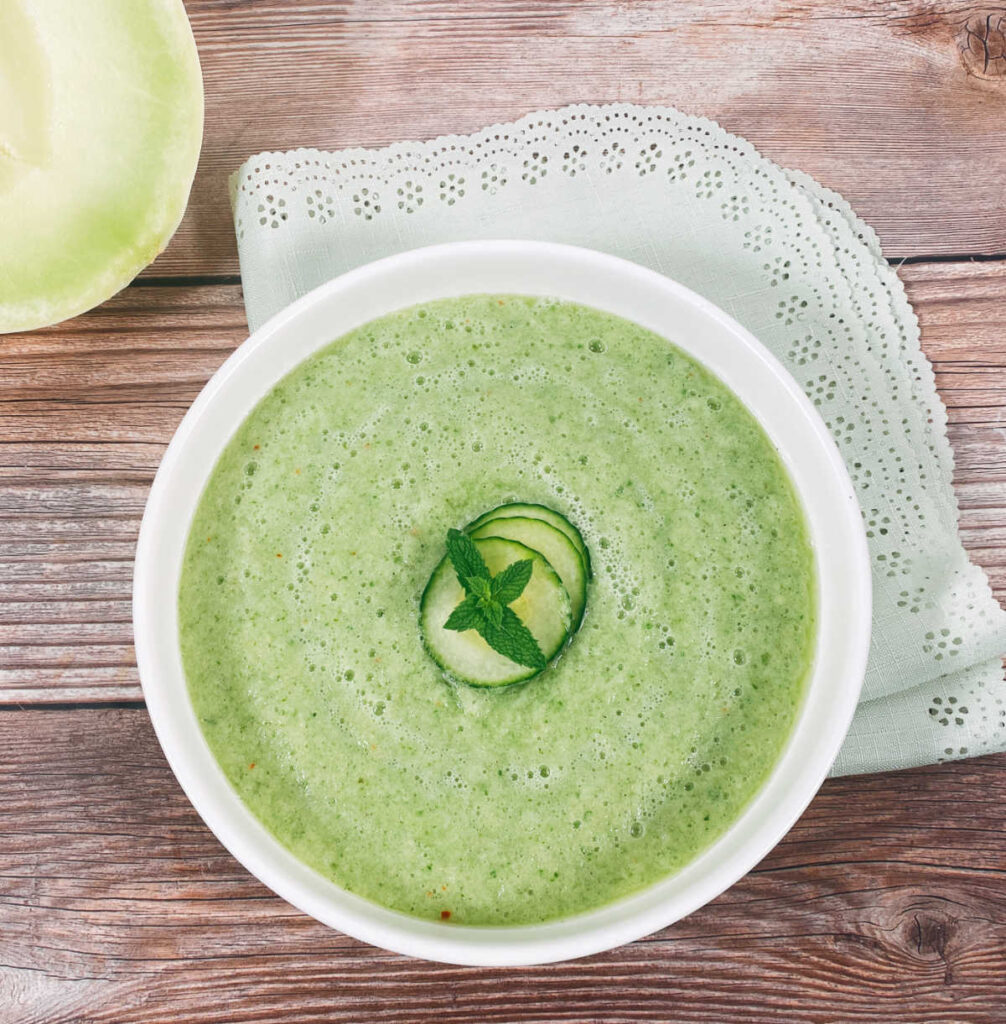 overhead image of soup in a shallow white bowl on a wooden background. Soup is garnished with mint leaves and thinly sliced cucumber.