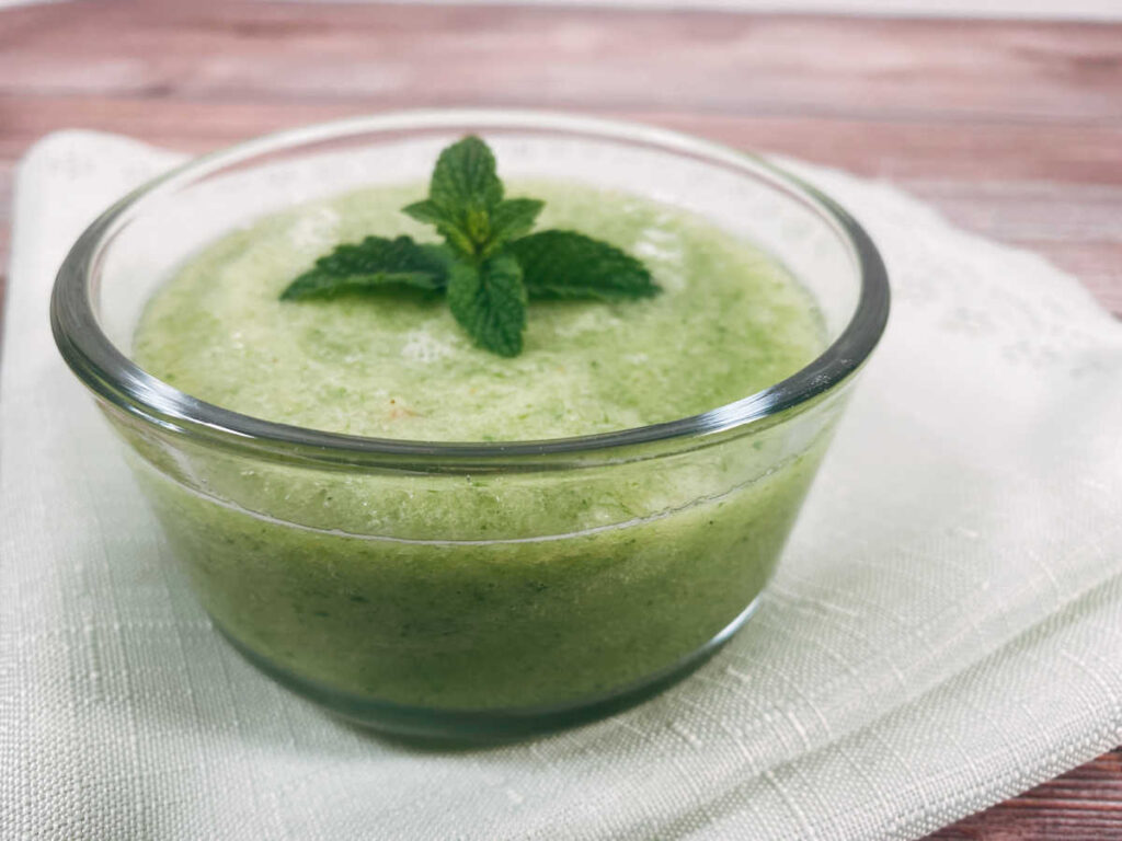 close up image of soup in a glass bowl on a light green scalloped napkin.