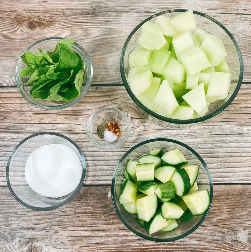 ingredients for the recipe sit in glass bowls on a wooden background