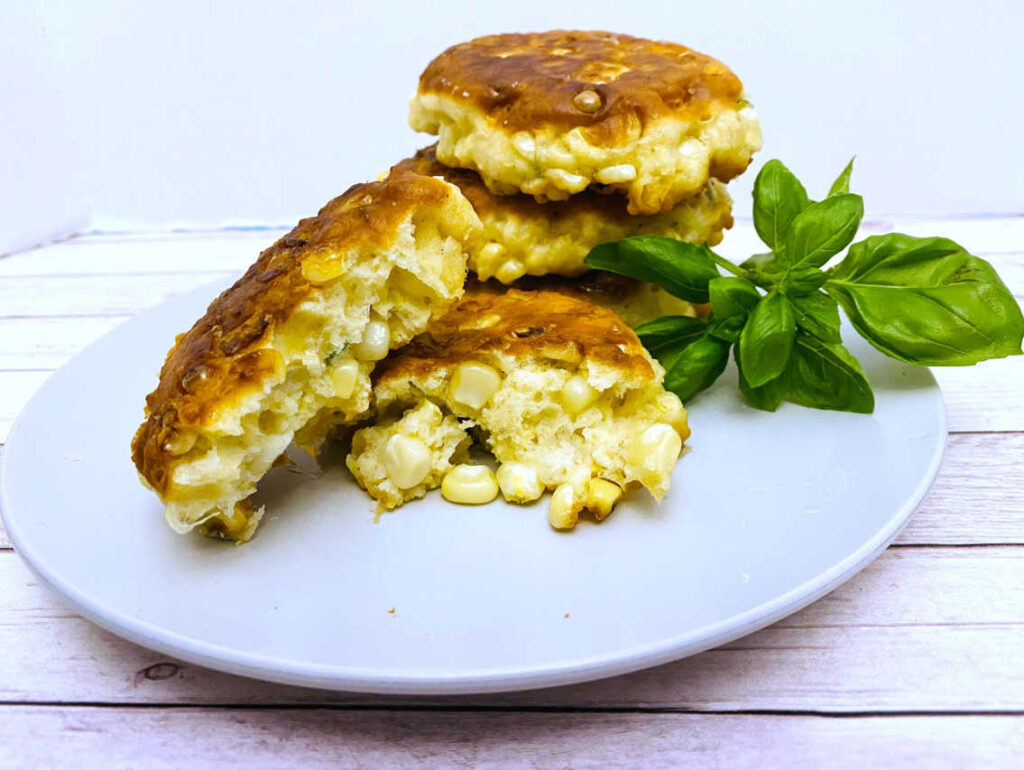 corn fritters sit on a white plate garnished with basil. one fritter is broken open to show all of the corn inside.