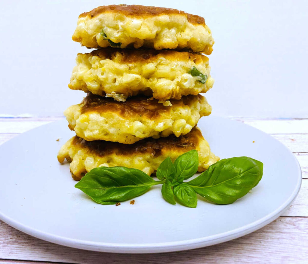 a tall pile of corn fritters sits on a white plate with a basil garnih.