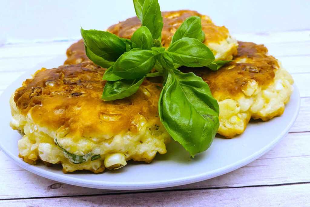 corn fritters are stacked on a white plate and garnished with fresh basil on top.