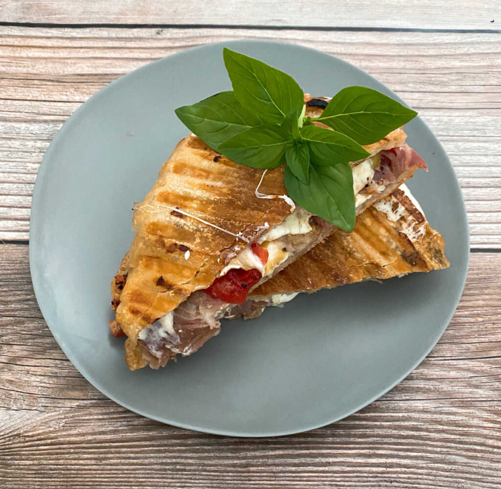 grilled panini, sliced in half and topped with fresh basil, sits on a blue-gray plate on a wooden background