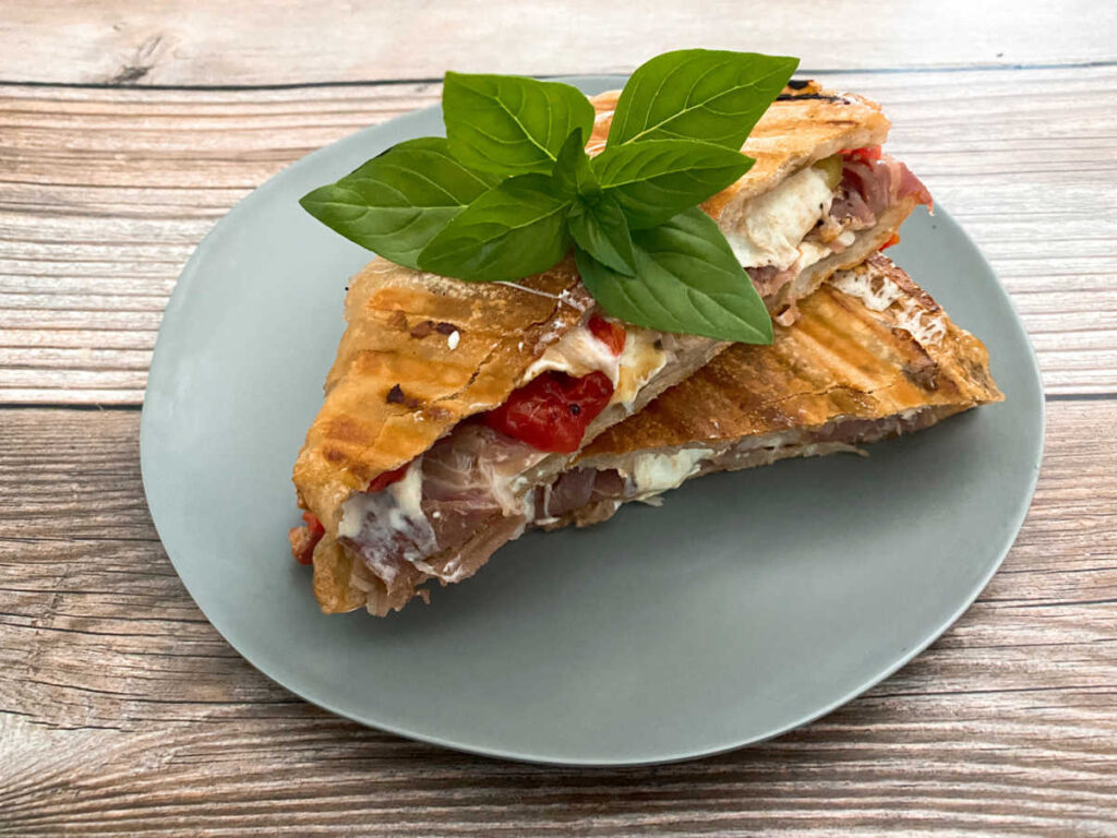 overhead image of the panini sliced in half and topped with a sprig of fresh basil