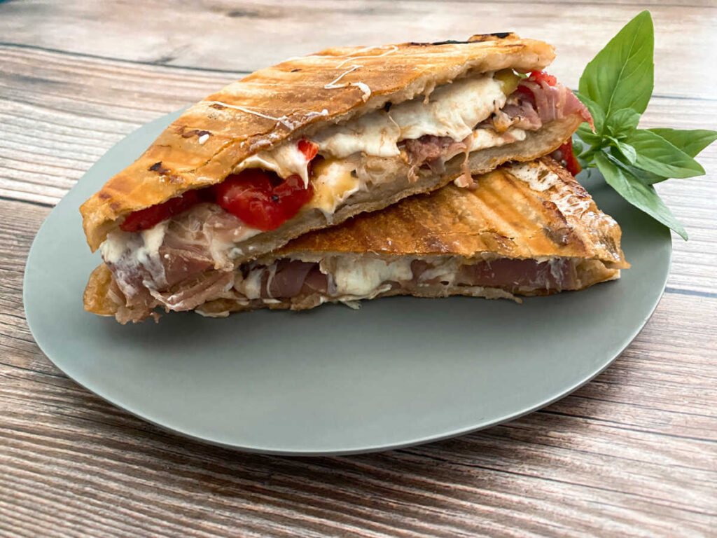 Panini is sliced in half and stacked on top of each other to show the filling of the sandwich.