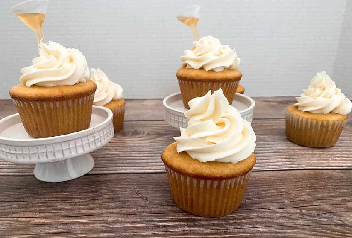 cupcakes sit on a wooden background and on white cupcake stands.