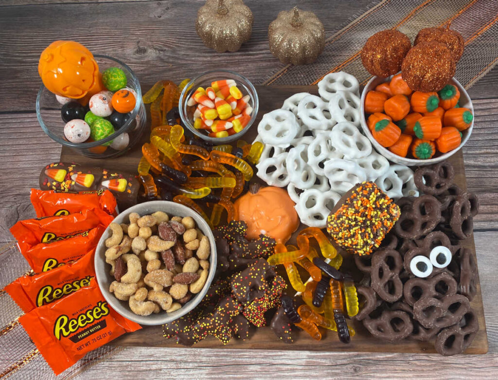 candy, pretzels, gumballs, nuts, marshmallows and other halloween candy sit on a wooden board. Area around the board is decorated with glittery pumpkins.