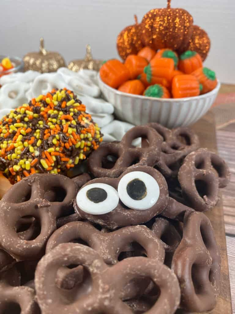 Close up image of candy eyeballs on chocolate covered pretzels.