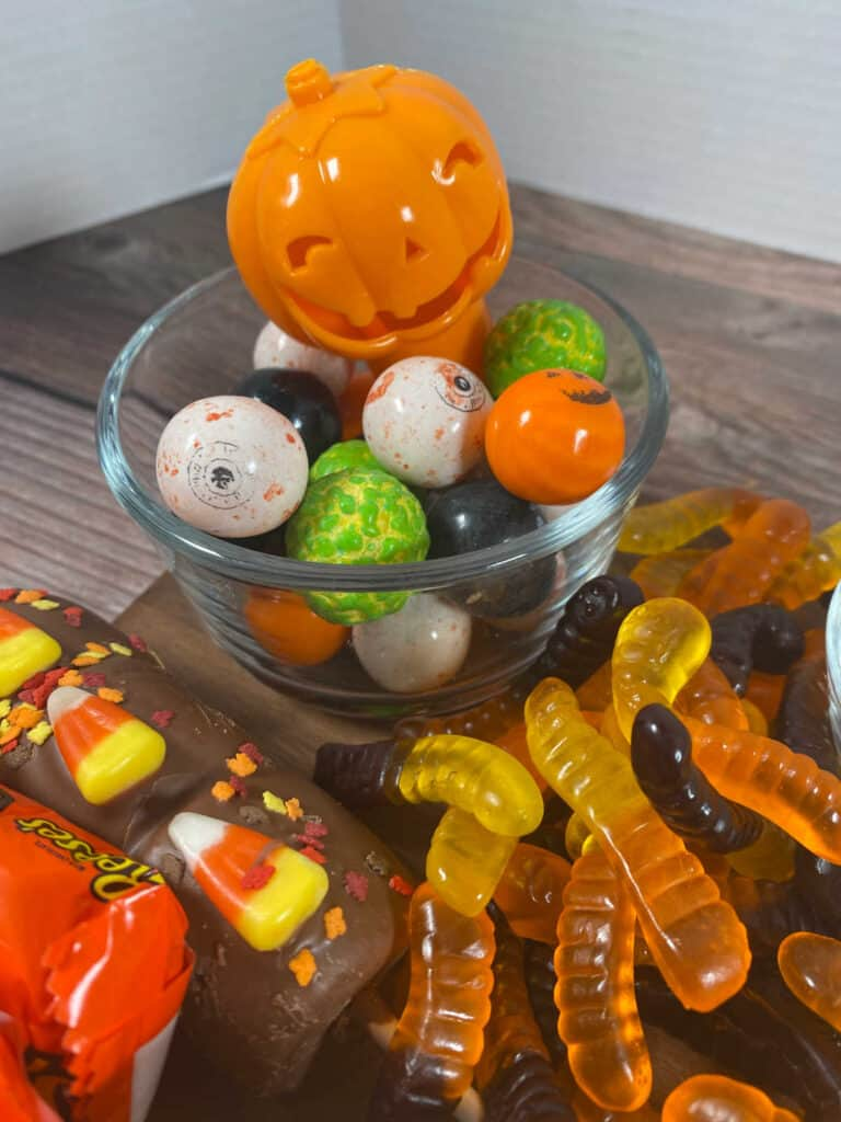 close up image of the halloween colored gumballs and gummy worms on the board.