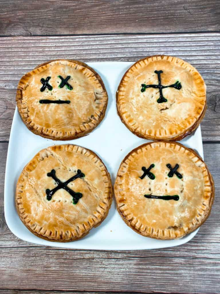 hand pies decorated to indicate they're poisonous sit on a square white plate on wooden background.