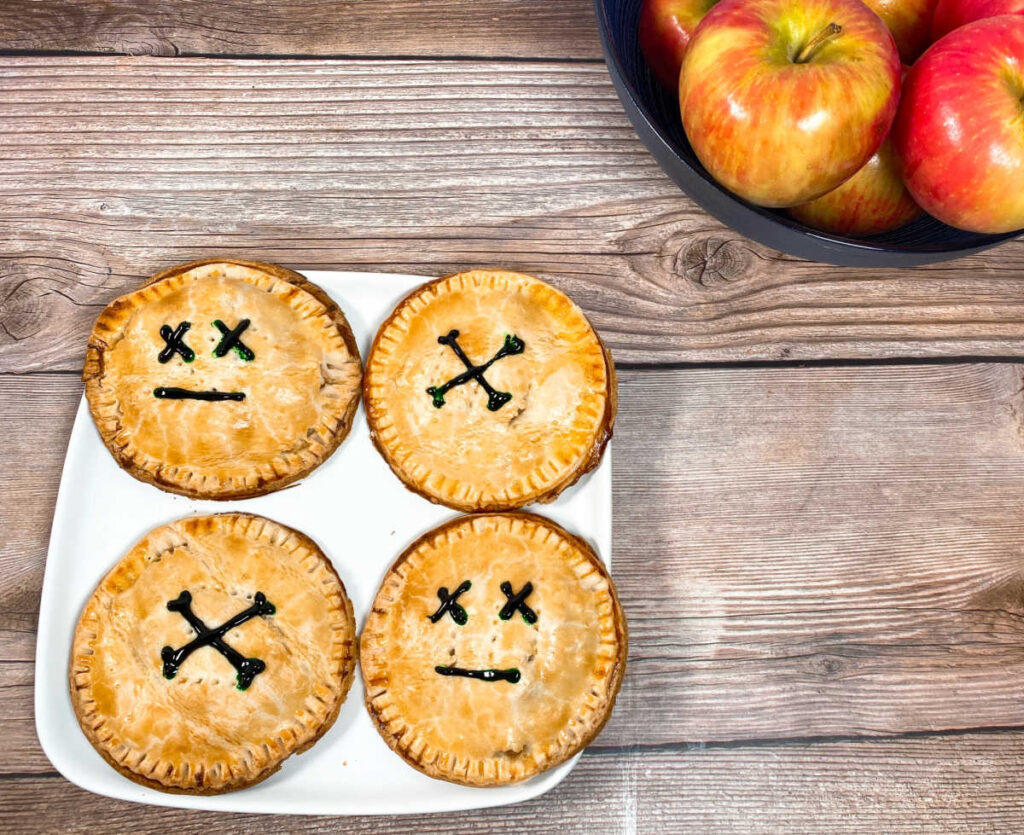 decorated hand pies sit on a white plate on a wooden background with a bowl of apples to the right side of them.